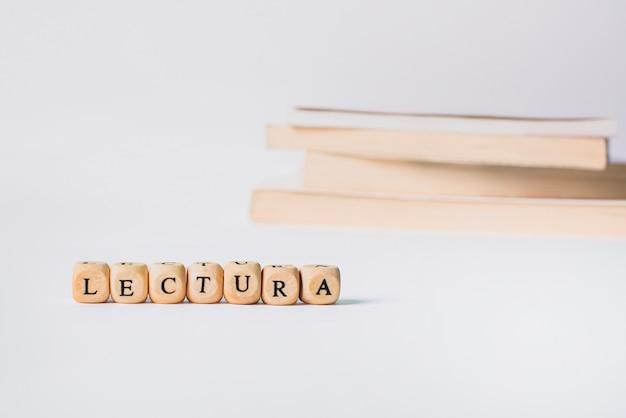 Woord in houten letters met boeken geïsoleerd op wit