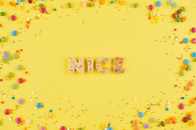 Woord leuk gemaakt met zelfgemaakte suikerkoekjes op gele achtergrond versierd met snoepjes en hagelslag