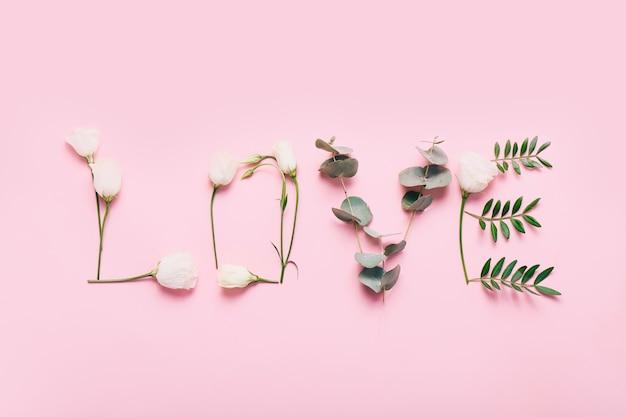 Woord liefde gemaakt van bloemen en bladeren op roze.