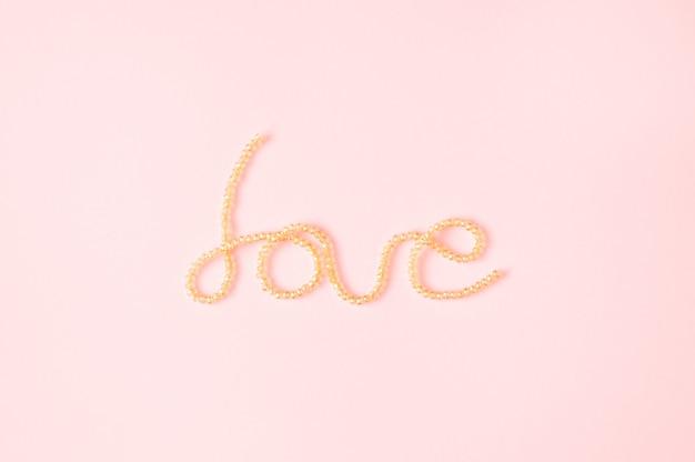 Woord liefde geschreven met glanzende parels op een lichtroze achtergrond. minimale fotografie