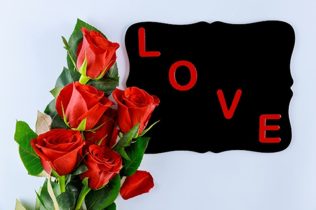 Woord liefde op zwart bord en boeket van mooie rode rozen. valentijnsdag of moederdag.