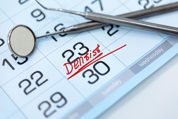 Woord tandarts op de kalender en tandheelkundige instrumenten close-up