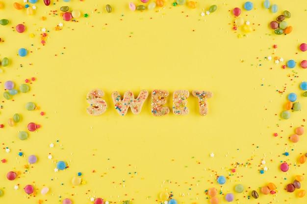 Woord zoet gemaakt van koekjesdeeg en versierd met hagelslag op felgele achtergrond