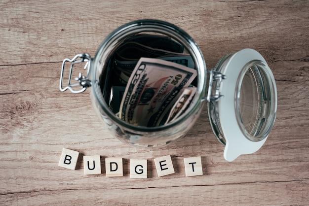 Woordbegroting en dollarbankbiljetten in glaskruik