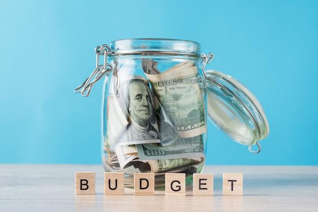 Woordbegroting en dollarrekeningen in glaskruik op blauw