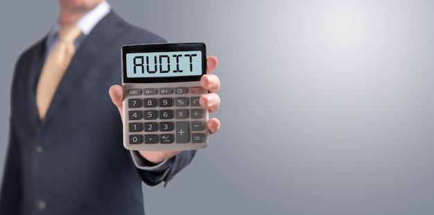 Woordcontrole op rekenmachine. zakenman toont rekenmachine met woord audit op het scherm. belasting, boekhouding, statistiek en analytisch onderzoek, business en finance concept. kopieer ruimte