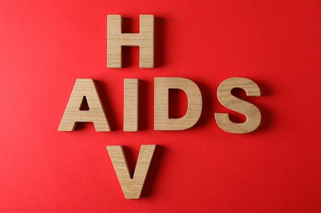 Woorden aids en hiv op rode muur, ruimte voor tekst