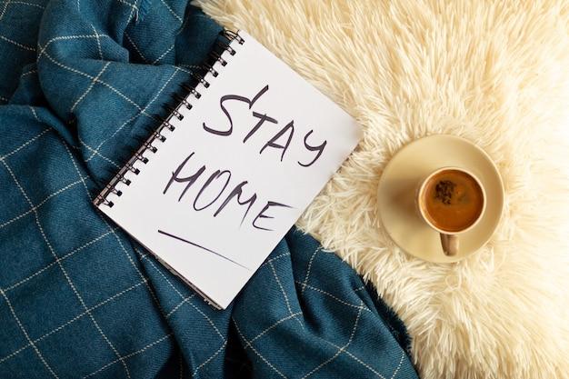Woorden blijf thuis is geschreven in notitieboekje, koffie. concept van zelfquarantaine thuis als preventieve maatregel tegen virusuitbraak. kantoor aan huis concept. bovenaanzicht
