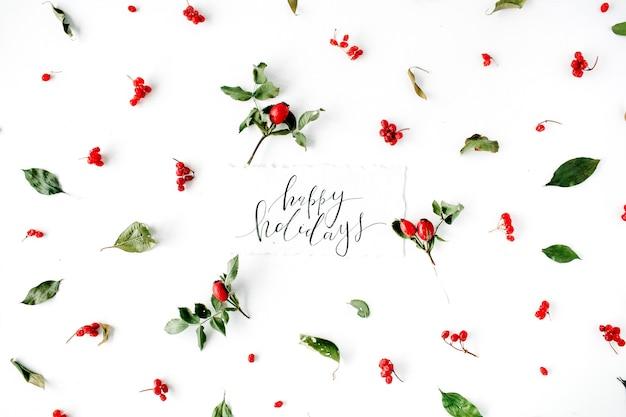 Woorden prettige feestdagen en minimaal creatief bessen arrangement patroon op wit.
