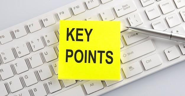 Woorden sleutelpunten geschreven op stickers op een computertoetsenbord