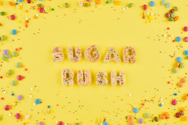 Woorden suiker haast van cookie alfabet op heldere gele achtergrond met kleurrijke snoepjes