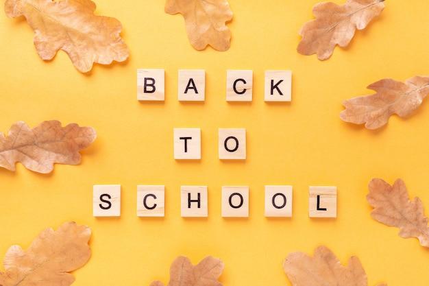 Woorden terug naar school en droge eikenbladeren op gele tafel