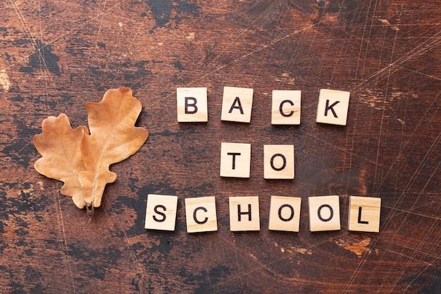 Woorden terug naar school en droge eikenbladeren op houten tafel