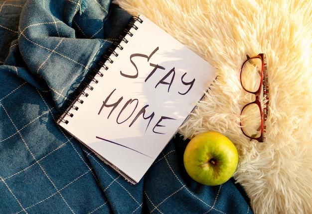 Woorden thuis blijven is geschreven in notitieboekje, concept van zelfquarantaine thuis als preventieve maatregel tegen virusuitbraak. kantoor aan huis concept. plat leggen