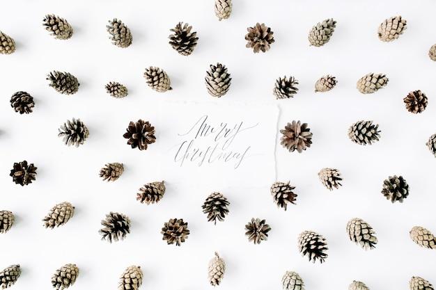 Woorden vrolijk kerstfeest en minimaal creatief kegel arrangement patroon op wit.
