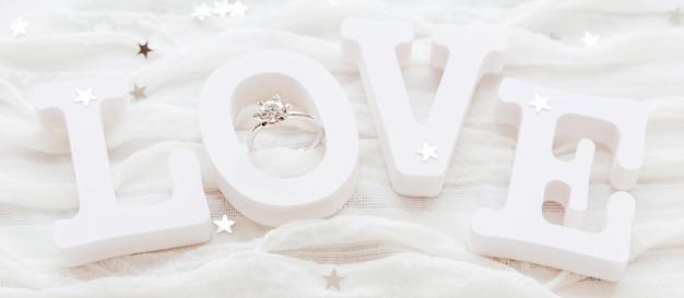 Woordliefde op witte stof met diamanten verlovingsring. goed voor valentijnsdag kaarten.