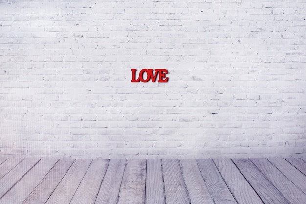 Woordliefde van houten letters op de muur van witte baksteenachtergrond