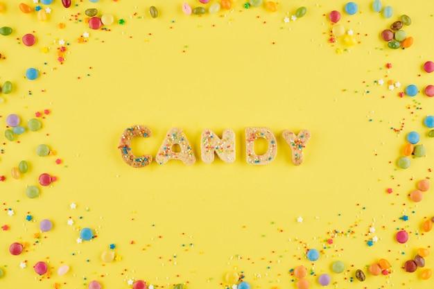 Woordsnoep gemaakt van suikerkoekjes en versierd met kleine hagelslag op felgele achtergrond