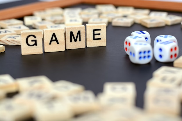 Woordspel met houten letters op zwart bord met dobbelstenen en brief in de cirkel