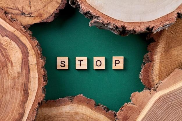 Woordstop en houten plakjes. stop met het snijden van bomen concept.