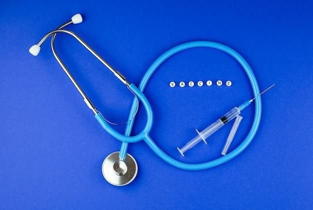 Woordvaccin, stethoscoop, spuit op blauw