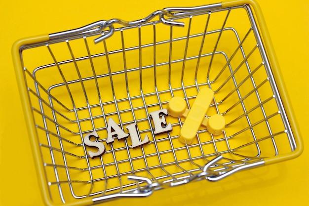 Woordverkoop en een procentpictogram onder aan een winkelmandje op gele achtergrond