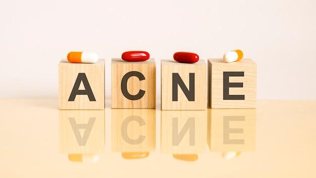 Word acne is gemaakt van houten kubussen op een gele achtergrond met pillen. medisch concept van behandeling, preventie en bijwerkingen