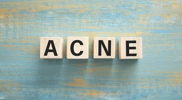 Word acne van kubussen op houten achtergrond. huid zorg concept