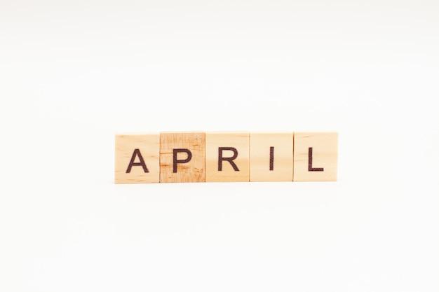 Word april gemaakt van houten blokken geïsoleerd