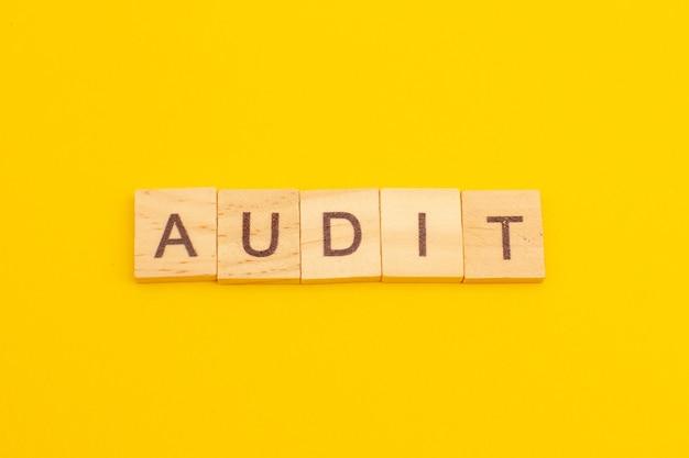 Word audit gemaakt van houten kubussen als bedrijfsconcept