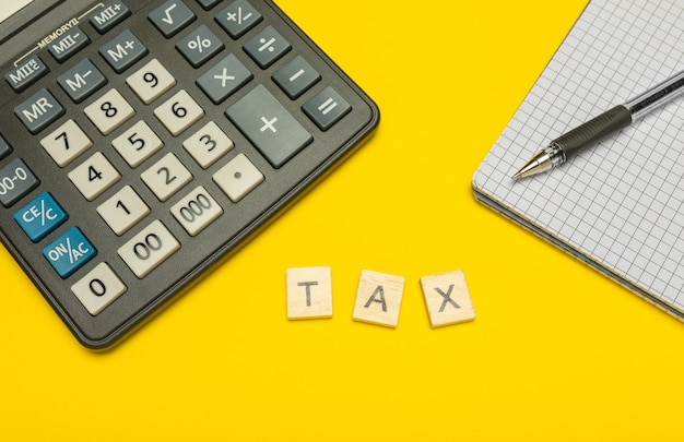 Word belasting gemaakt met houten letters op gele en moderne rekenmachine met pen en notitieboekje.