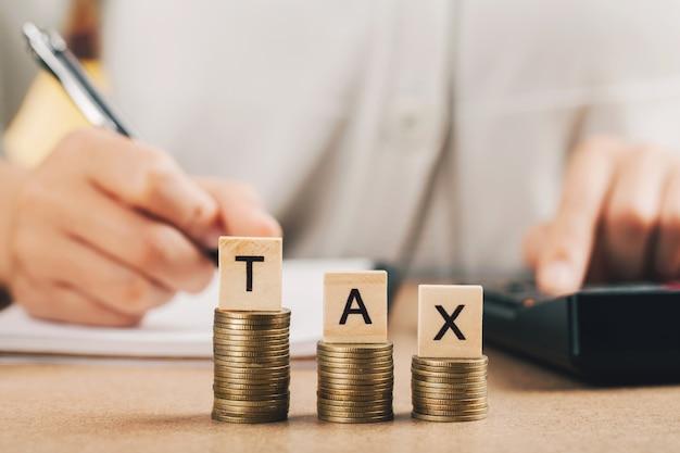 Word belasting op stap gestapelde munten als grafiek omhoog over vrouwen geld tellen met behulp van calculator.