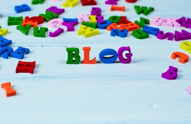Word blog van kleine veelkleurige houten letters op een witte ondergrond