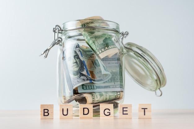Word budget en dollarbiljetten in glazen pot