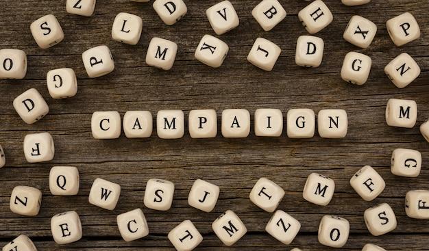 Word campagne geschreven op houtblok, voorraadbeeld