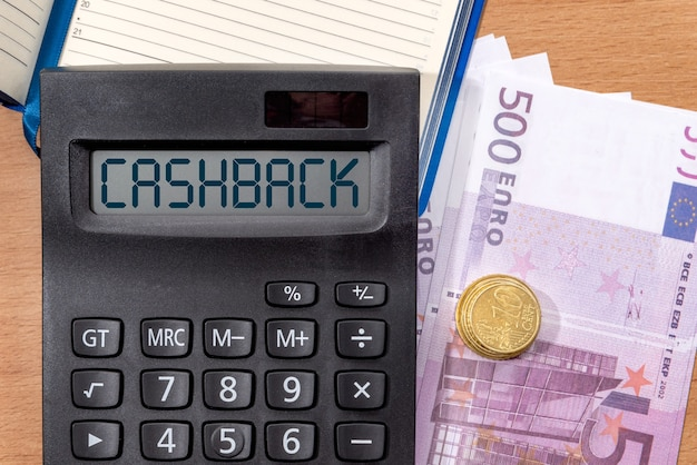 Word cashback op het display van een rekenmachine over kantoortafel met bankbiljetten euro. geld, financiën en bedrijfsconcept