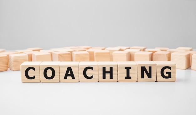 Word coaching geschreven op hout blok. bedrijfsconcept.