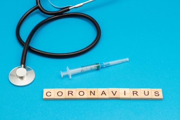 Word coronavirus gemaakt van houten kubussen op blauw met een stethoscoop en chirurgische spuit