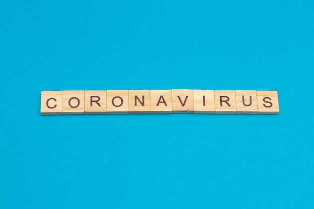 Word coronavirus gemaakt van houten kubussen op blauw