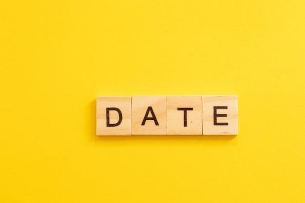 Word date gemaakt van houten letters op gele achtergrond.