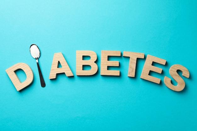 Word diabetes gemaakt van houten letters op turquoise tafel