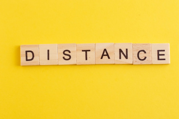 Word distance gemaakt van houten letters op gele achtergrond.