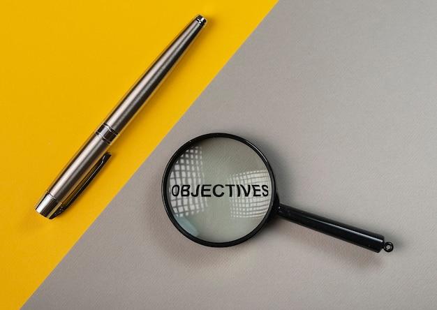 Word doelstellingen door vergrootglas op geel en grijs achtergronddoelconcept