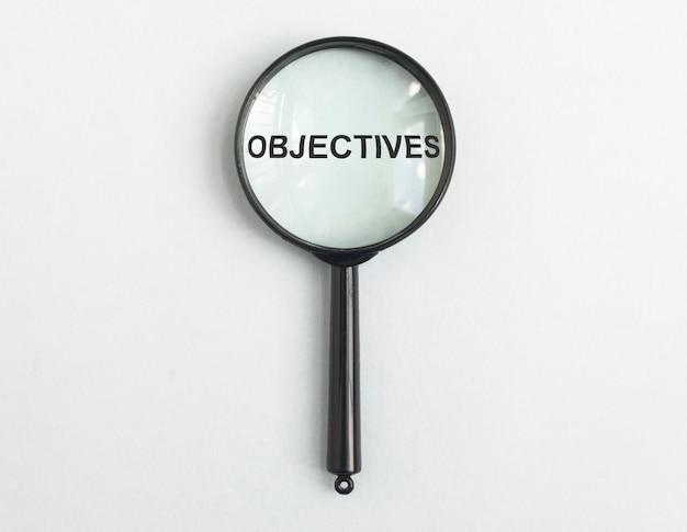 Word doelstellingen door vergrootglas op lichtblauw gary achtergronddoelconcept