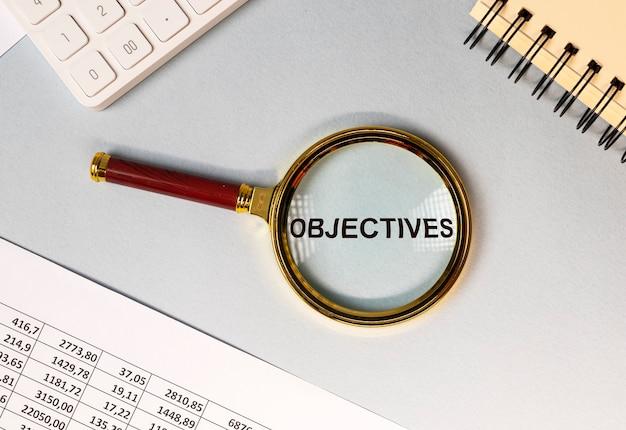 Word doelstellingen door vergrootglas op office desk top view bsiness doelconcept