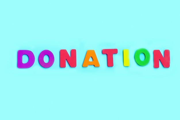 Word donation gemaakt van kleurrijke letters op blauwe muur.