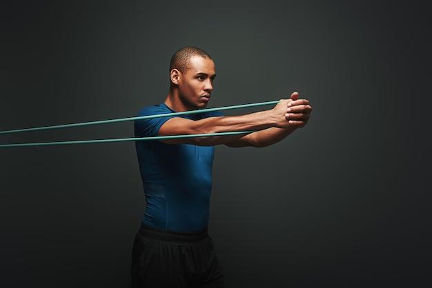 Word elke dag sterker sportman die traint met een weerstandsband over een donkere achtergrond