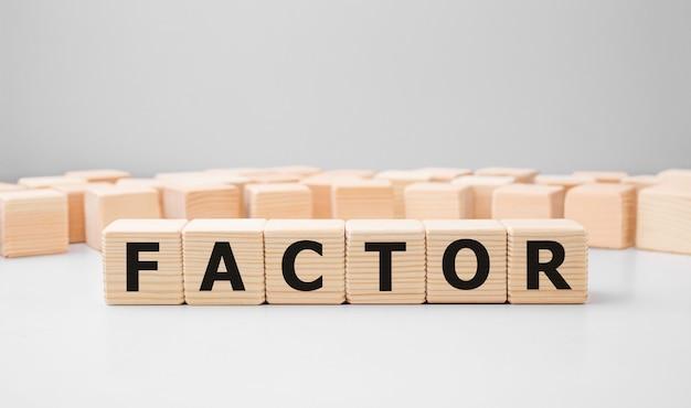 Word factor gemaakt met houten bouwstenen