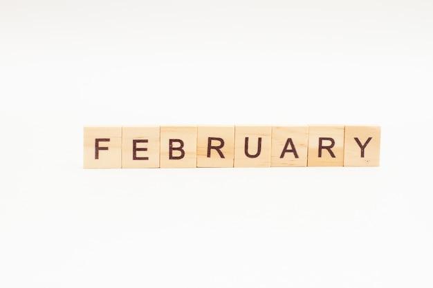Word februari gemaakt van houten blokken geïsoleerd