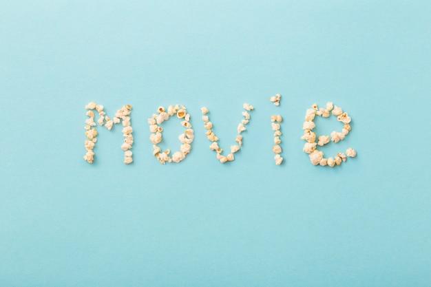 Word-film gemaakt van popcorn op blauwe achtergrond